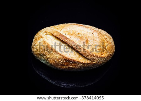 Top down view closeup on potato bread roll, isolated on black background with reflection. - stock photo