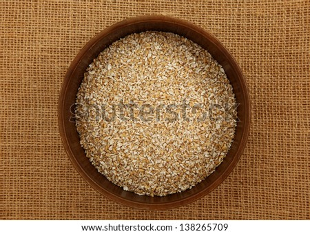 Top Down View Of A Bowl Of Steel Cut Irish Oatmeal On Burlap Bag - stock photo