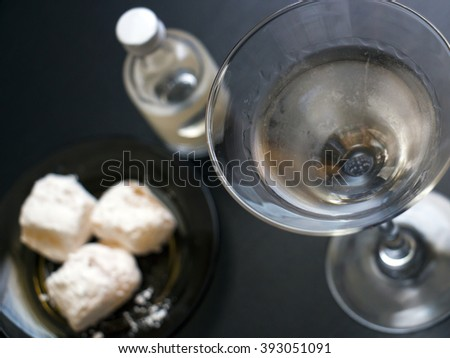 Top down view of a martini cocktail drink with small bottle and a plate with Turkish delight sweets.