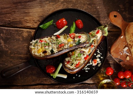 Top down view of a stuffed aubergine with couscous or quinoa on a brown vintage wooden background - stock photo
