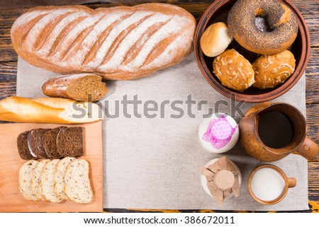 Top down view of bread loaves, slices, rolls, bagels and milk bottles on cloth over wooden table - stock photo