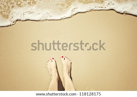 top down view of feet waiting for a wave to come in, oh the anticipation! copy space too. - stock photo