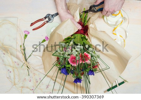 Top down view of florist's hands working on a beautiful bouquet over his work table. - stock photo