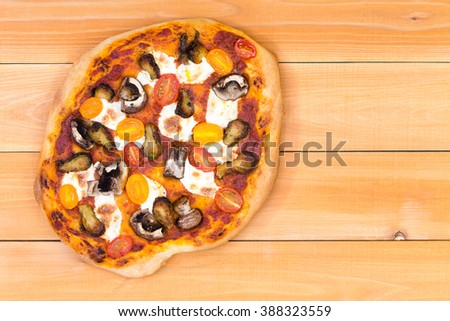 Top down view of freshly baked personal sized vegetarian pizza topped with mushrooms and yellow cherry tomatoes over wooden picnic table - stock photo