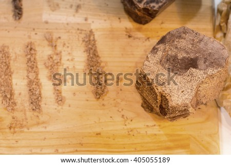 Top down view of large chocolate block with shavings or crumbs arranged in vertical lines over wooden cutting board - stock photo