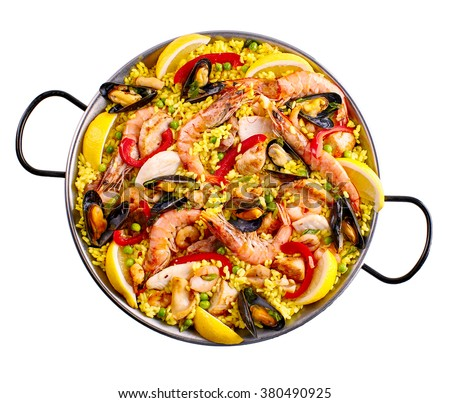 Top down view of paella margarita prepared with yellow rice, shrimp, clams and lemon wedges over white background - stock photo