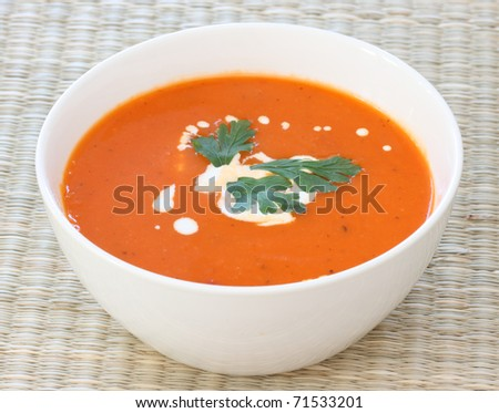 Top down view of red tomato soup in white bowl, sprinkled with cream - stock photo