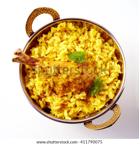 Top down view of single Indian spicy chicken drumstick and fluffy yellow rice with tasty cilantro leaf on top over white surface with gray shadow - stock photo