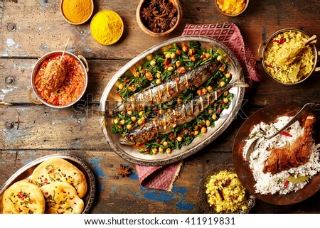 Top down view on baked fish indian style surrounded by rice, bread, sauces and various spices on weathered wooden surface - stock photo