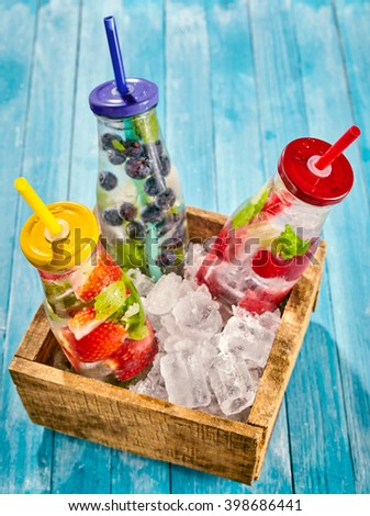 Top down view on bottles full of ice water and strawberries, blueberries and raspberries in a little box on top of wooden table - stock photo