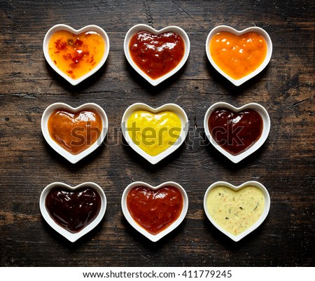 Top down view on nine colorful mild and spicy sauces and marinades filled up inside heart shaped bowls over weathered wooden table - stock photo