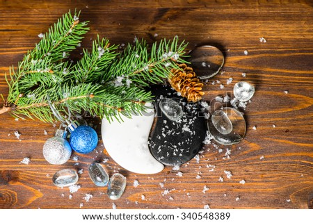 top down winter concept of Chinese New Year with Yin-Yang symbol, cones, blue, silver balls, fir tree, ice and snow, closeup - stock photo