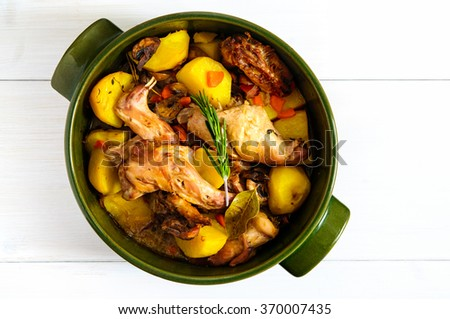 Top flat view of roasted rabbit meat with vegetables and herbs  in round ceramic pot on white wooden table surface, copy space - stock photo