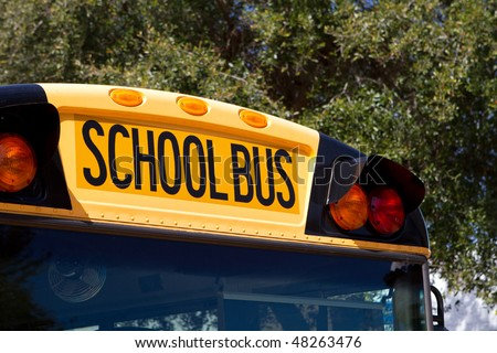 Top front of a yellow school bus with red and amber lights. - stock photo