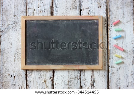 top image of chalkboard and colorful chalks over wooden table  - stock photo