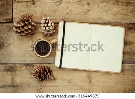 top image of open notebook with blank pages, next to pine cones and cup of coffee over wooden table. retro filtered image  - stock photo