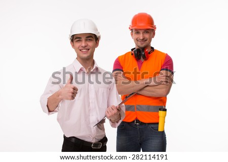 Top manager and builders of his company ready to perform basic tasks requiring physical labour on construction sites. Worker in orange jacket smiling. - stock photo