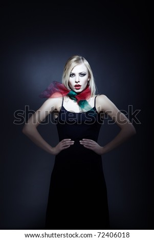 Top model in elegant dress with perfect makeup on a dark background - stock photo