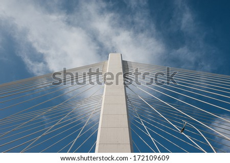 Top of a bridge with white clouds and blue background