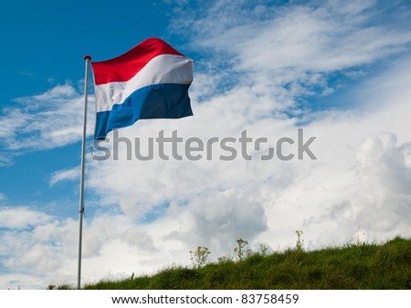 Top of a dike in the Netherlands with the Dutch national flag waving in the wind - stock photo