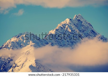 Top of a mountain peaks through the clouds in New Zealand with Instagram style filter - stock photo