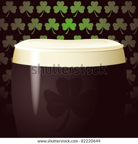 Top of a pint glass with black stout beer and foam, with Irish shamrock background and a touch of a shamrock on the pint glass itself - stock photo