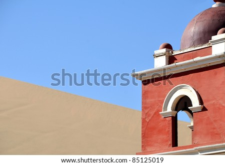 Top of a red church tower against desert in Huacachina Oasis near Ica - Peru