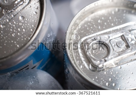 Top of aluminum cans of soda pop covered in ice and droplets of water - stock photo