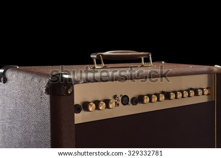 top of brown Electric guitar amplifier on black background - stock photo