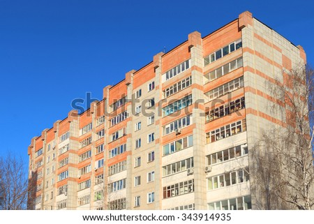 Top of high residential building with balconies and trees at sunny winter day - stock photo