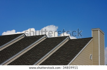 Top of house with multiple roof lines and blue sky in background - stock photo