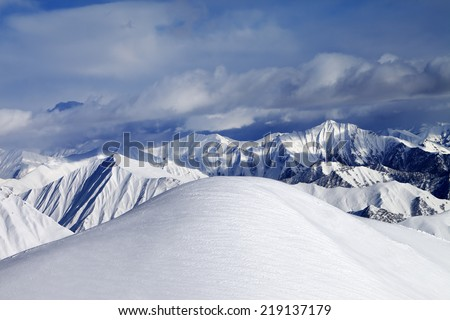 Top of off-piste snowy slope and cloudy mountains. Caucasus Mountains, Georgia, ski resort Gudauri. - stock photo