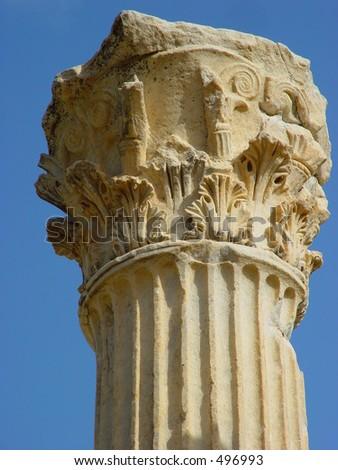 Top of roman pillar against clear blue sky - stock photo