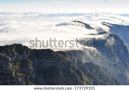 Top of Table Mountain covered by clouds, sunset time - stock photo
