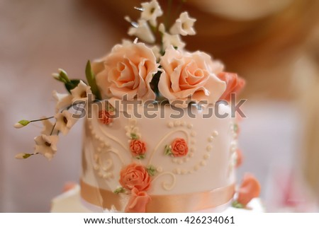 Top of tasty sweet wedding white cake dessert decorate by beautiful delicious icing sugar pink roses and ribbon  - stock photo