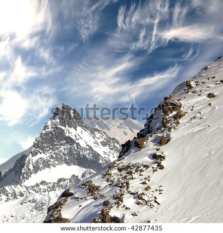 Top of the Caucasus mountain range. Against the background of the sky. Slope with traces of snowboarders and skiers. Deserted winter landscape.