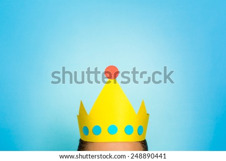 Top of the head of a woman wearing golden yellow crown. Content marketing is queen / king concept. - stock photo