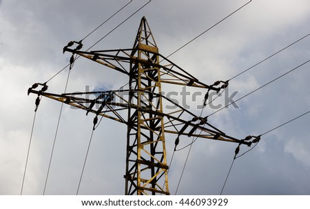 Top of the high voltage tower (electricity post) against cloudy sky. - stock photo