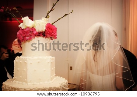 top of the wedding cake with bride and groom kissing - stock photo