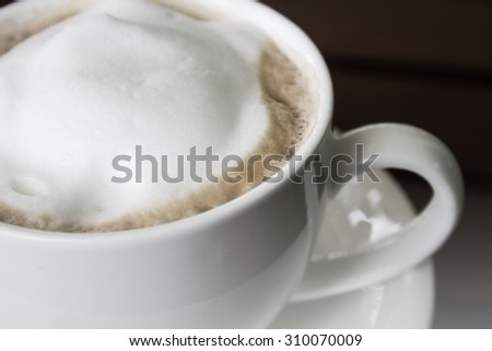 Top of view cappuccino coffee on wood table focus at  white foam - stock photo