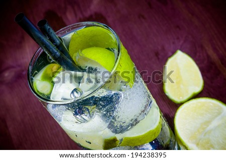 top of view of cocktail glass with ice and lime slice on wood table - stock photo