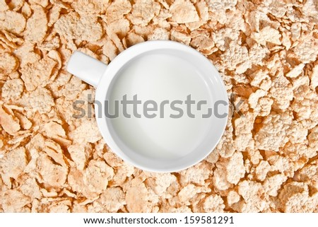 top of view of cup of milk on corn flakes background, breakfast concept - stock photo