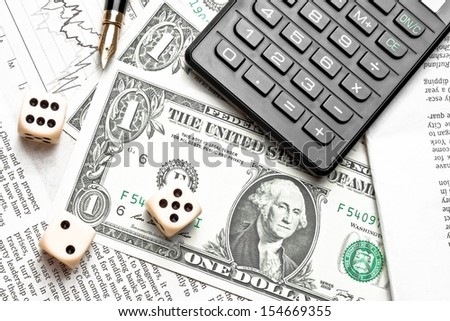 top of view of dice on financial chart near dollars and calculator on white table - stock photo
