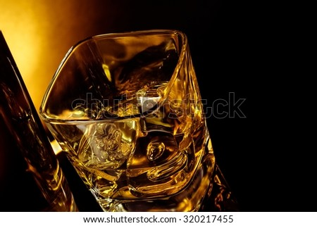 top of view of glass of whiskey near bottle on black table with reflection, warm light time of relax with whisky with space for text - stock photo