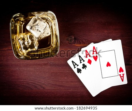 top of view of poker playing cards near whiskey glass on old wood table - stock photo