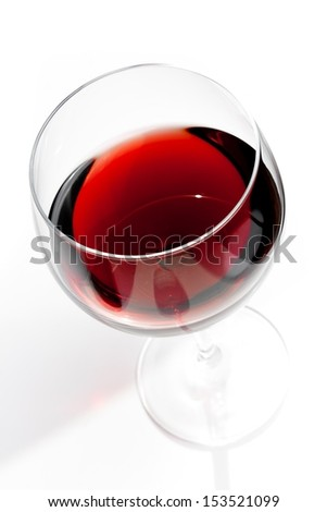 top of view of red wine glass under daily light on white table - stock photo