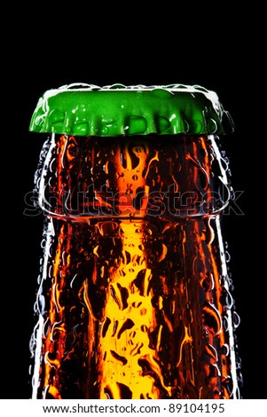 Top of wet beer bottle isolated on black - stock photo