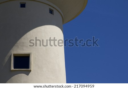 Top of white water tower against a blue sky. - stock photo
