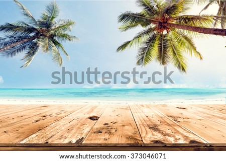 Top of wood table with blurred sea and coconut tree background - Empty ready for your product display montage. Concept of beach in summer - stock photo