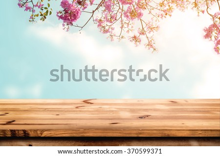 Top of wood table with pink cherry blossom flower on sky background - Empty ready for your product display or montage.  - stock photo